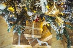 Подарки обернутые в бумаге под зеленым деревом и белыми концами игл Стоковые Изображения RF