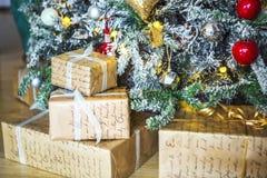 Подарки обернутые в бумаге под зеленым деревом и белыми концами игл Стоковые Фотографии RF
