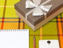 Подарок блокнота Smartphone на таблице стоковое изображение