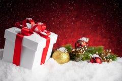 Подарок и безделушки рождества на красной предпосылке bokeh Стоковое Изображение