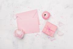 Подарок или присутствующая коробка, розовый бумажный пробел и лютик цветут на белой таблице сверху для wedding модель-макета или  стоковое фото