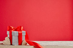 Подарок на деревянном столе с красной предпосылкой Стоковые Изображения