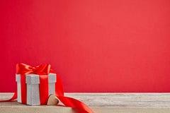 Подарок на деревянном столе с красной предпосылкой Стоковые Изображения RF