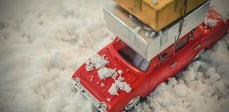 Подарок на рождество нося автомобиля игрушки на поддельном снеге Стоковое Изображение