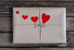 Подарок обернутый в бумаге kraft с красными сердцами Стоковое Фото