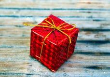 Подарок обернутый красным цветом на деревянной предпосылке Стоковое Фото