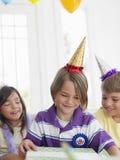 Подарок отверстия мальчика с гостями на партии Стоковые Фото