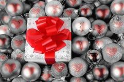 Подарок рождества и красные безделушки сердца Стоковая Фотография