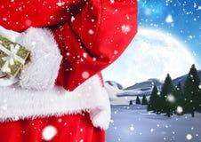Подарок рождества Санты пряча за его назад Стоковая Фотография