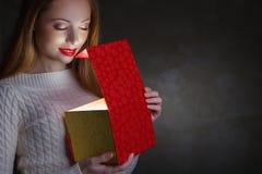 Подарок рождества. Счастливая коробка отверстия девушки Стоковые Фотографии RF