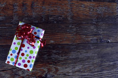 Подарок рождества с красным смычком в деревянном столе Стоковое Изображение