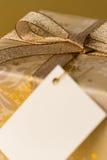 Подарок рождества с пустой лентой золота бирки Стоковые Фотографии RF
