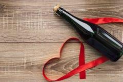Подарок, сердце и бутылка красного вина на романтичный день ` s валентинки праздника Стоковые Изображения
