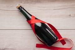 Подарок, сердце и бутылка красного вина на романтичный день ` s валентинки праздника Стоковая Фотография