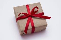 Подарок с красной лентой на белой предпосылке Стоковая Фотография