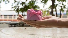 Подарок с розовой лентой, белой коробкой в женских руках, сюрпризом рождества, счастливым Новым Годом Стоковое Изображение RF