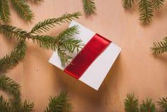 Подарок ювелирных изделий рождества с красной лентой и елевыми ветвями Стоковое фото RF