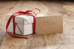 Подарочная коробка белой бумаги с тонкой красной лентой и карточка 8-ое марта бумажная на старой деревянной таблице Стоковое Изображение RF