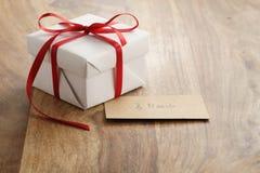 Подарочная коробка белой бумаги с тонкой красной лентой и карточка 8-ое марта бумажная на старой деревянной таблице Стоковое фото RF