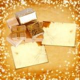 Подарочная коробка в упаковочной бумаге золота на предпосылке картона Стоковая Фотография