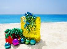 Подарочная коробка и подарок кладут в мешки на пляже - концепции праздника Стоковые Фотографии RF