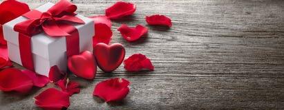 Подарочная коробка и пук красных роз на древесине Стоковые Фотографии RF
