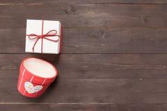 Подарочная коробка и цветочный горшок на деревянной предпосылке с пустой Стоковые Изображения RF