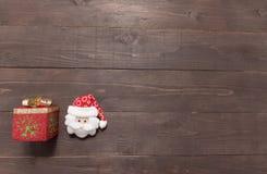 Подарочная коробка и santa на деревянной предпосылке с пустым космосом Стоковое Изображение RF