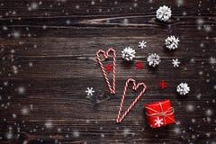 Подарочная коробка, конусы сосны и конфета рождества тросточки на темных деревянных животиках Стоковое Изображение