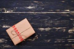 Подарочная коробка обернутая в коричневой бумаге и связанная с веревочкой Стоковое Фото
