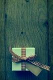 Подарочная коробка обрабатываемая крестом на древесине сверху Стоковое Изображение