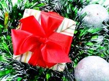 Подарочная коробка присутствующая с красной предпосылкой рождества ленты Стоковая Фотография