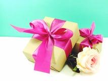 Подарочная коробка присутствующая с розовым смычком ленты и красивой предпосылкой цветков Стоковое Изображение RF