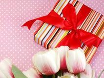 Подарочная коробка присутствующая с розовым смычком ленты и красивой предпосылкой цветков Стоковое Изображение