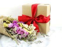 Подарочная коробка ремесла бумажная с смычком ленты и букет цветка с текстурой ткани Стоковая Фотография
