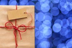 Подарочная коробка с биркой на предпосылке запачканных светов Стоковое Изображение