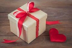Подарочная коробка с красной лентой и красное сердце на деревянной предпосылке стоковые изображения