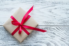 Подарочная коробка с красной лентой на деревенской предпосылке Стоковые Изображения