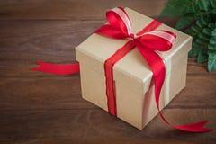 Подарочная коробка с красной лентой на деревянной предпосылке стоковые фото