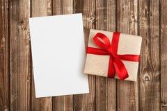 Подарочная коробка с красными лентой и чистым листом бумаги Стоковое Изображение