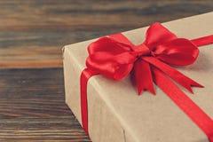 Подарочная коробка с красным смычком на древесине Стоковая Фотография RF