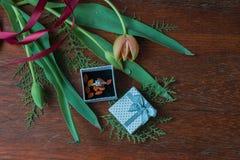 Подарочная коробка с тюльпанами и травами и обручальными кольцами на деревянном wa стоковое фото rf
