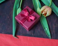 Подарочная коробка с тюльпанами на деревянной стене стоковые фотографии rf