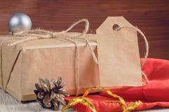 Подарочная коробка упаковала коричневую бумагу и шпагат с пустой биркой украсил аксессуары праздника на деревянном столе Стоковое Изображение RF
