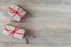 2 подарочной коробки с красными лентами, 2 зажимками для белья на деревянном backgro Стоковая Фотография