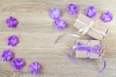 2 подарочной коробки, фиолетовые цветки на деревянной предпосылке с пустым курортом Стоковые Фотографии RF