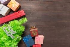 Подарочные коробки и рождественская елка на деревянной предпосылке с empt Стоковое фото RF