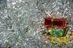 Подарочные коробки на серебряных пушистых украшениях Стоковая Фотография