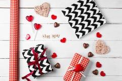 Подарочные коробки обернутые в красной, черно-белой бумаге с конфетой Стоковая Фотография