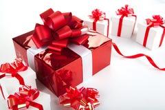 Подарочные коробки одной красной подарочной коробки белые на сером цвете Стоковые Фото